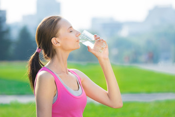 Portrait of woman drinking water after sport