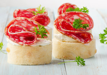 Baguette with salami and cream cheese with herbs.