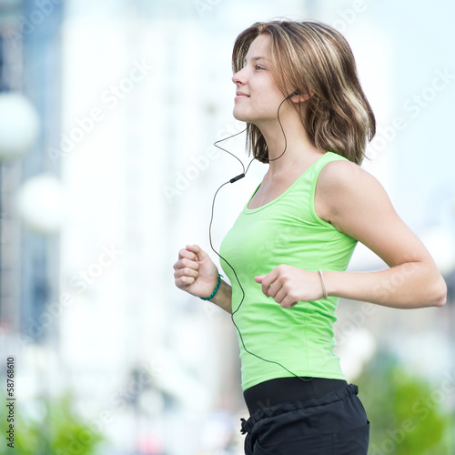 Woman jogging in city street park.