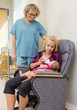 Nurse Looking At Woman Feeding Newborn Babygirl On Chair