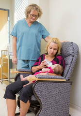 Nurse Looking At Woman Feeding Newborn Babygirl On Chair