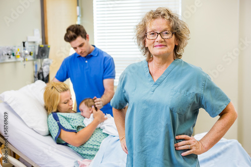 Mature Nurse Standing With Couple And Newborn Baby In Background - 58769639