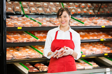 Happy Saleswoman Holding Meat Packages At Counter