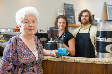 Woman Holding Coffee Cup With Workers At Counter