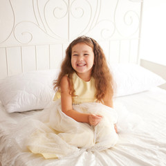 Happy smiling child waking up in the morning.