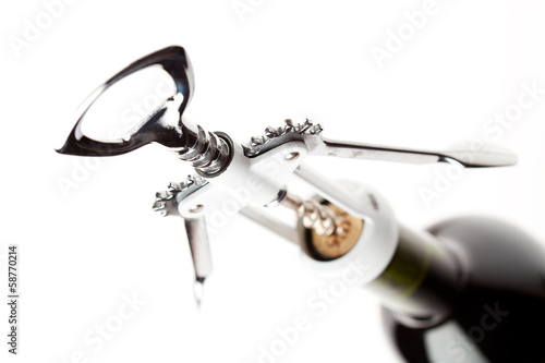 Opening bottle of wine with corkscrew, on white background
