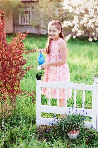Beautiful girl watering spring flowers