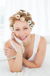 Beautiful woman in hair curlers using phone in bed