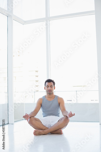 Full length of a young man sitting in lotus pose