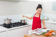 Woman looking at recipe book and preparing food in kitchen