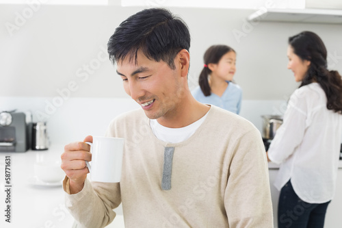 Smiling man drinking coffee with family in background