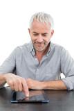 Smiling mature businessman using digital tablet at desk