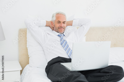 Relaxed businessman looking at laptop in bed