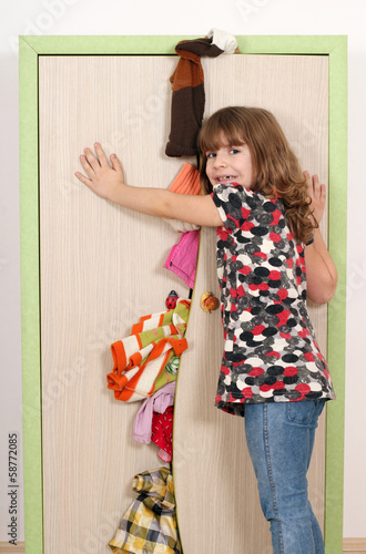 upset little girl trying to close the closet