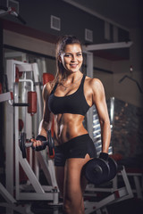 Sexy athlete with a dumbbell in the gym