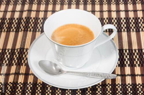 a cup of coffee on bamboo mat