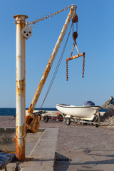 White fishing boat and small crane in port of Petrovac town, Mon