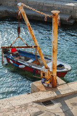 Old fishing boat and small crane in port of Petrovac town, Monte