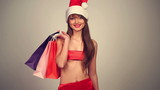Sexy girl in santa claus hat with shopping bag