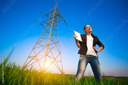 pretty businesswoman in a field with a laptop