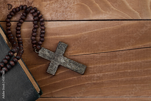 Iron cross with a book on a wooden surface