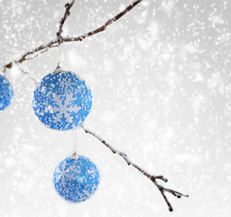 Christmas balls hanging on snowy branch