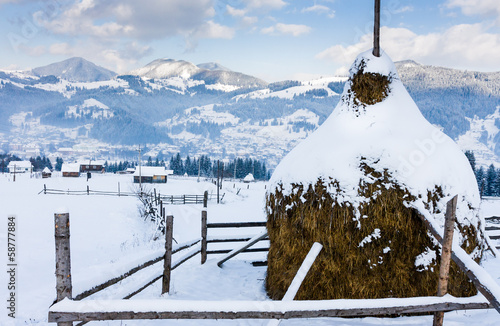 Snowy haystack on a background of a village in the mountains