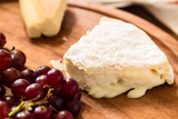 cheese on wooden plate with grapes