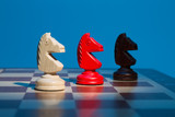 Three chess knight on chessboard on blue background