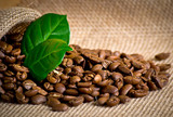Coffee grains with bag and leaves on sackcloth
