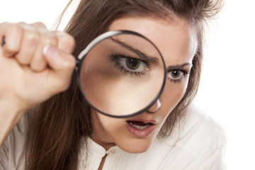 shocked young woman looking through a magnifying glass