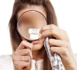 woman read through a loupe the label for care in her panties