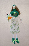 Handmade doll with a bird on the hand in a dress and sweater on
