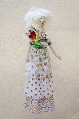 Handmade doll with a flower in his belt in a long white dress on