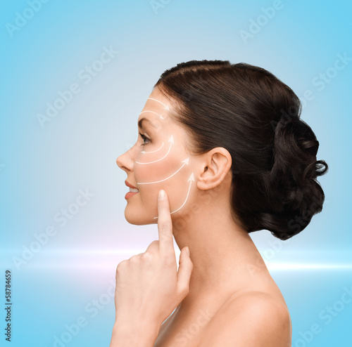 smiling young woman pointing to her cheek