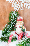 Cute wooden Santa claus standing in snow
