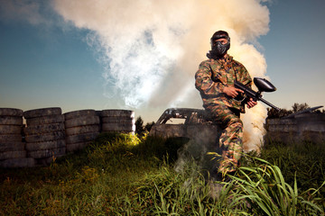 Paintball player holding the position with smoke background