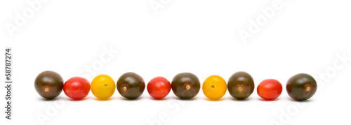 cherry tomatoes of different colors on a white background