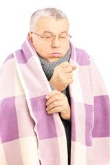 Senior man covered with blanket and neckwear coughing