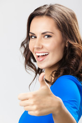 Young woman with thumbs up gesture, over grey
