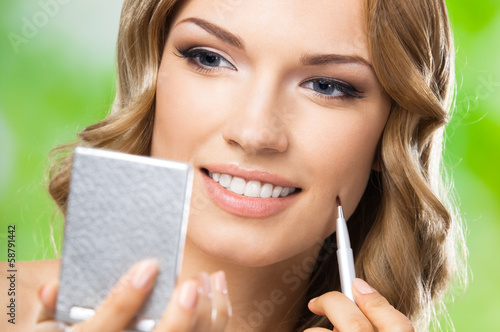 Smiling woman with make up brush, outdoor