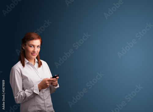 Young woman standing and typing on her phone with copy space
