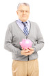 Confident senior gentleman holding a piggy bank