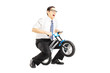 Excited young businessman riding a small bicycle