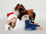 girl in the hat of Santa Claus with a horse