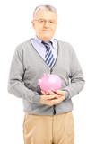 Confident senior gentleman holding a piggy bank