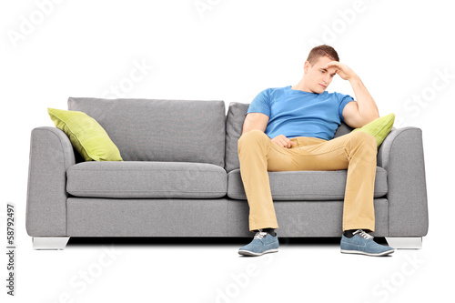 Dissappointed young man sitting on a sofa