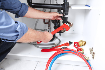 Hands of Plumber with a wrench.
