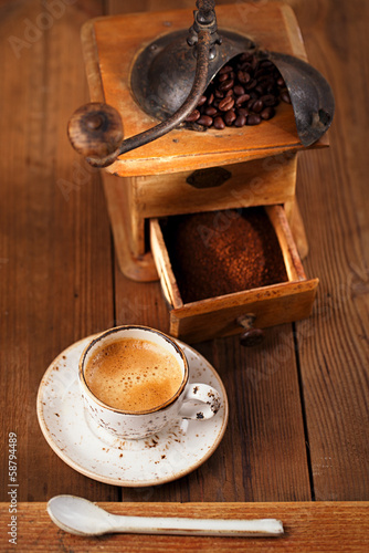 A cup of espresso coffee with Old coffee mill  textured table