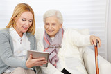 Woman giving senior woman introduction to internet